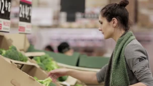 Mladá žena si vybírá zelí na pultech.