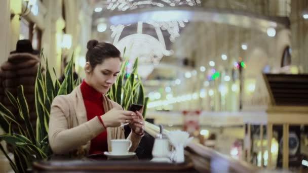 Žena pomocí smartphone, pití kávy v kavárně.