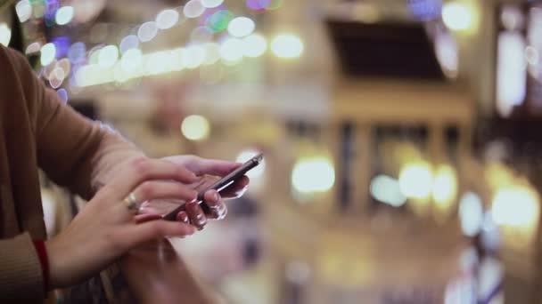 Žena ruce SMS, pomocí smartphone v obchoďáku