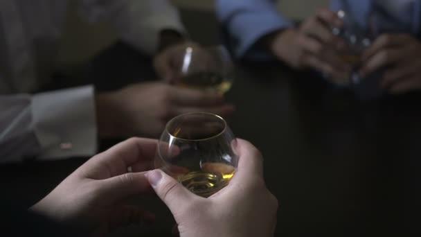 Tři stylové muži sedět u stolu, vysoké a drží sklenice na víno
