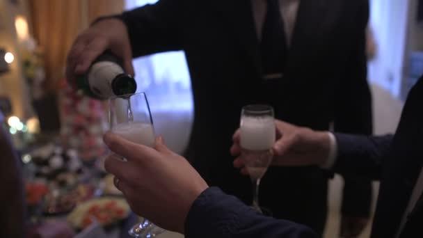 Moderní člověk naplní sklenice dvou mladých chlapců, šumivé víno bílé