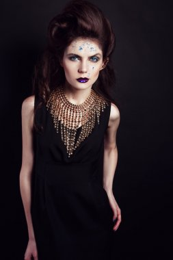 Closeup portrait with deep blue eye, creative makeup and golden accessories