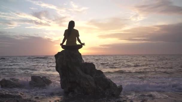 Jóga žena v lotosové pozici cvičí jógu a meditaci. venku na večerním oceánu