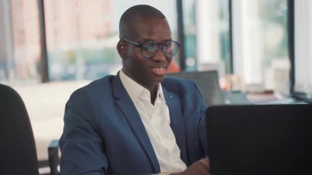 African ethnicity office worker working at computer indoors in office
