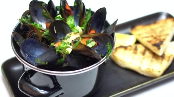 4k Video Bewegung der Pfanne mit gekochten Muscheln fertig zum Essen. Frische Meeresmehl.