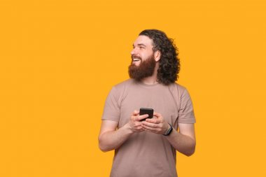 Photo of joyful bearded hipster man holding smartphone and looking away at copyspace.