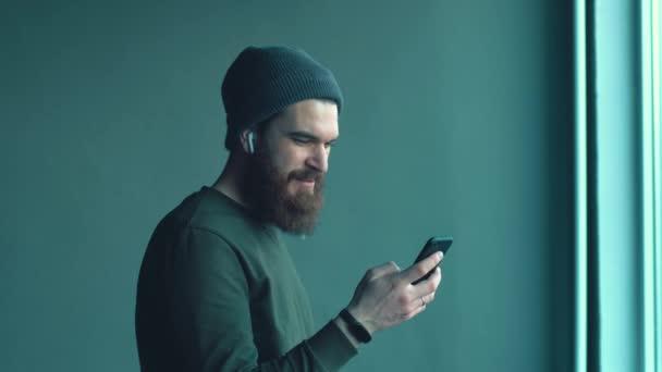 Footage of bearded hipster man using smartphone near big window