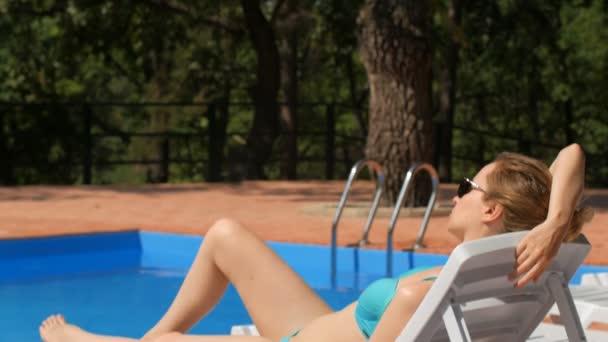 Blondine im blauen Badeanzug bekleidet sitzt in der Nähe vom Schwimmbad