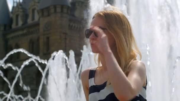 usměvavá blondýnka sedí na kašny poblíž hradu a dojemné sluneční brýle