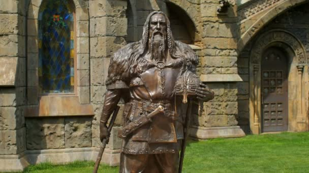 bronze statue of medieval knight on castle background