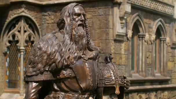 bronze statue of medieval knight half-turned on castle background