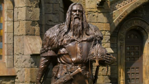 bronze statue of medieval old knight half-turned on castle background