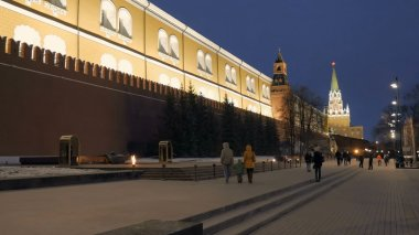 family is going to eternal flame near a wall of Moscow Kremlin in evening