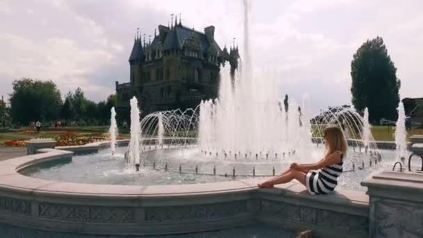 blondýna v pruhovaných šatech sedí na fontáně v slunečný den, poblíž hradu