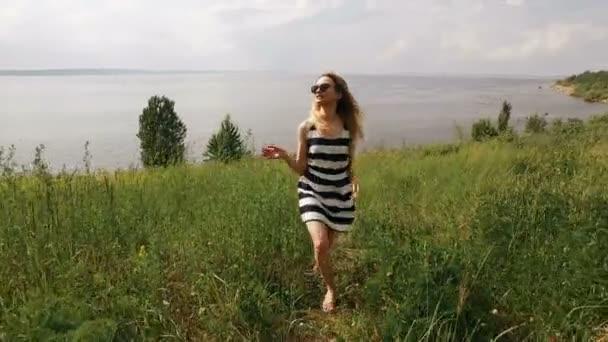 mladá dívka v sluneční brýle je chůze na poli, s úsměvem, dotykem chloupky