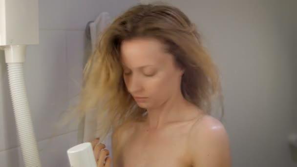 fiatal gyönyörű lány fürdőszobával-fen, haj szárító Hotel megérintette haját, lengő fej