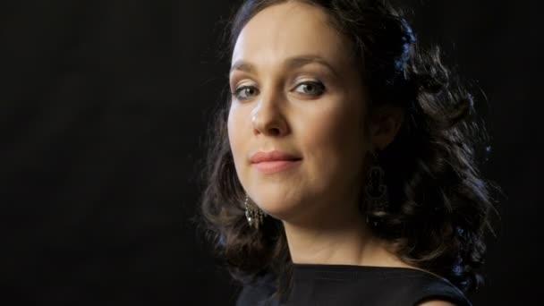 okouzlující mladá žena s vlnité tmavé vlasy při pohledu na fotoaparát a usmíval se, detail