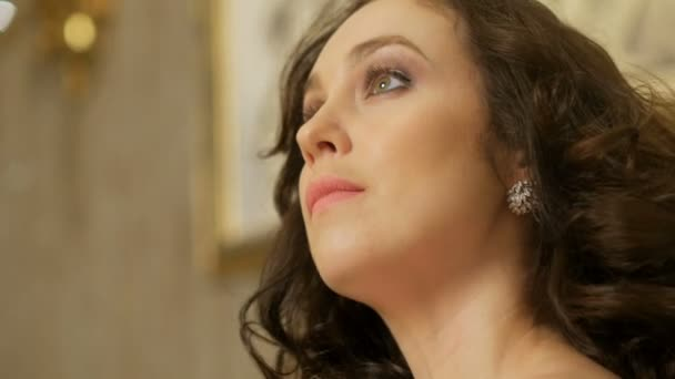 elegantní brunetka s kudrnatými vlasy, diamantové náušnice a živý makeup, vzhlédl, detail