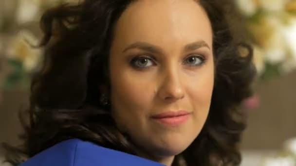 ventilátor fouká do vlasů krásná usměvavá brunetka, obrací hlavu, při pohledu na fotoaparát
