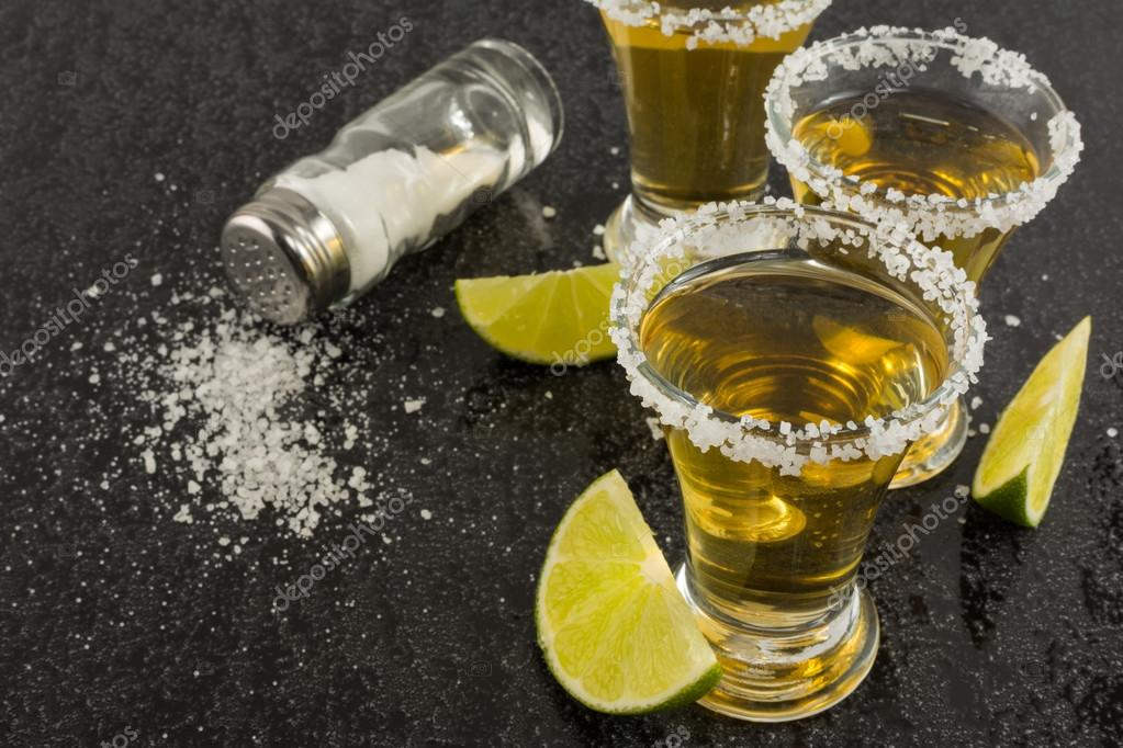 Gold tequila shots with lime on black background — Stock Photo ...