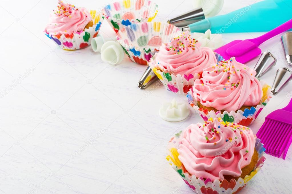 Cupcakes de cumpleaos rosa decoradas y utensilios de cocina Foto