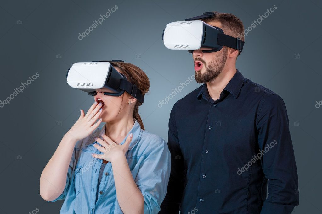 652c484c71a0 Excited young couple using a VR headset glasses and experiencing virtual  reality on grey blue background — Photo by nazarov.dnepr gmail.com