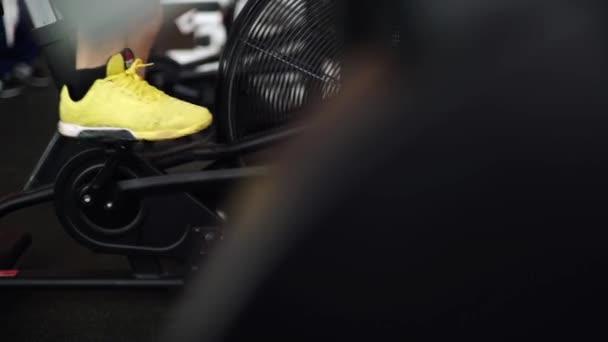 Boční pohled zblízka část mladíka v sportovní obuv na kole v tělocvičně. jezdec výstřel