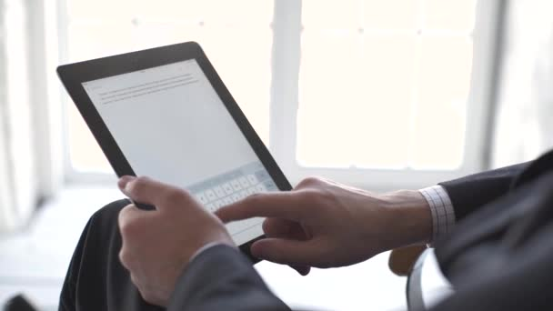 Detailní záběr mužských rukou dotýkajících se digitální tablety