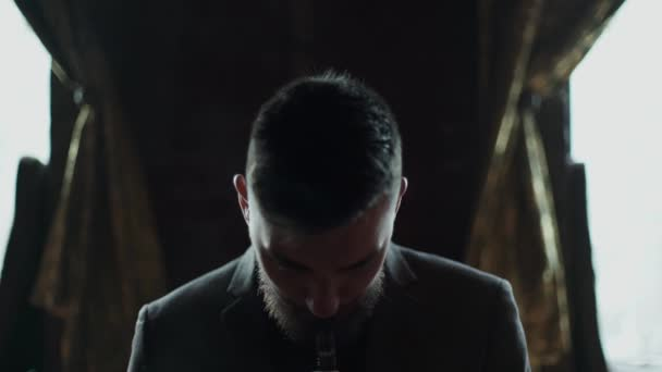 close-up of a bearded man in suit smoking electronic cigarette