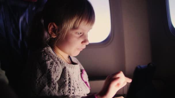 Kleines Mädchen spielt im Flugzeug mit dem Tablet