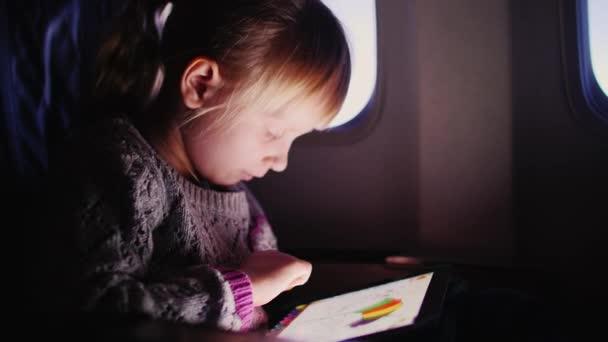 kleines Mädchen malt die Farbe auf den Teller an Bord des Flugzeugs