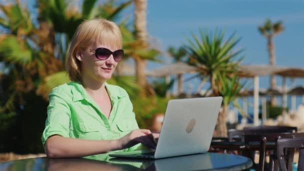 Žena v sluneční brýle požívá notebookem na pozadí rekreačních oblastí