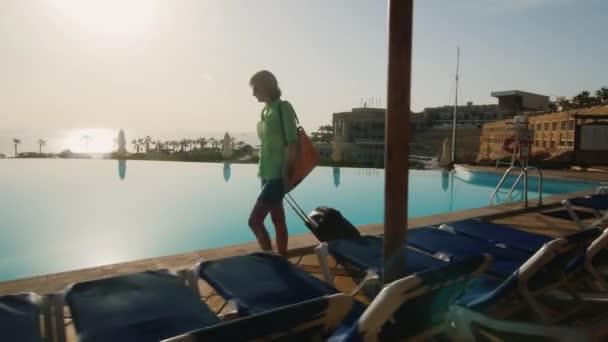 Silueta ženy, která vede podél bazénu. řízený cestovní tašku. Steadicam horké