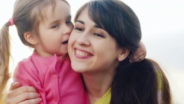 Girl three years, kisses his mom