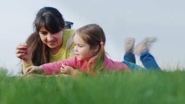 Žena s dívkou 3 roky leží na zelené trávě, chatování