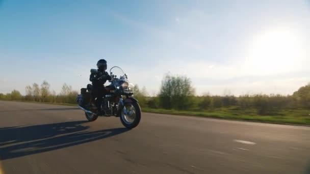 Motocykl jízda na venkovské silnici, slunce svítí na ní