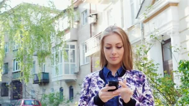 Lány megy keresztül a város, írja be a smartphone. A nap megvilágítja a gyönyörű