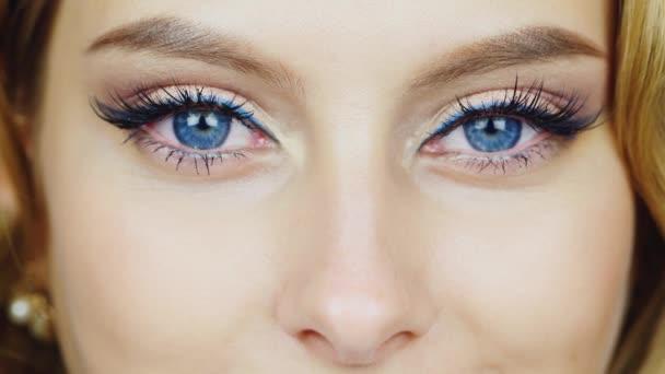 Modré oči mladé ženy dívá do kamery