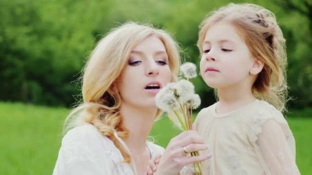 Mutter mit einer Tochter 4 Jahre stecken - Pusteblume wegpusten, lachen. Im Hintergrund ein malerischer grüner Rasen