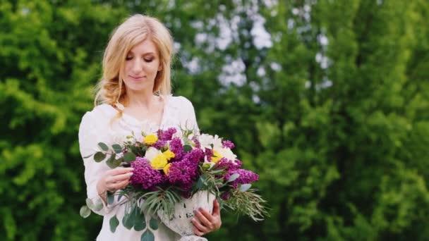 Krásná blondýnka s vůní šeříku. To stojí na pozadí zelených keřů