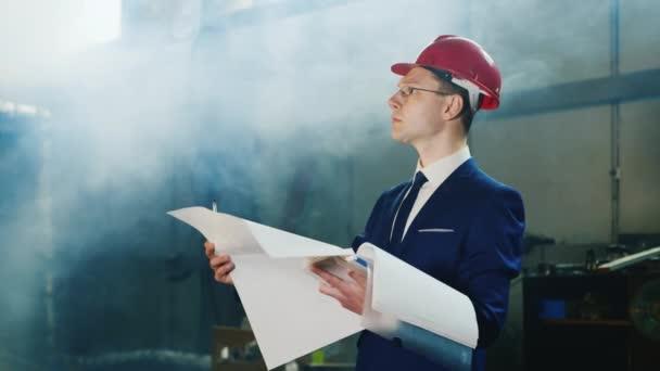Inženýr v obleku a helmu studuje plány interiéru