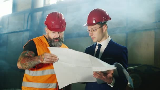 Architect and builder in a helmet with a beard together studying blueprints at a construction site