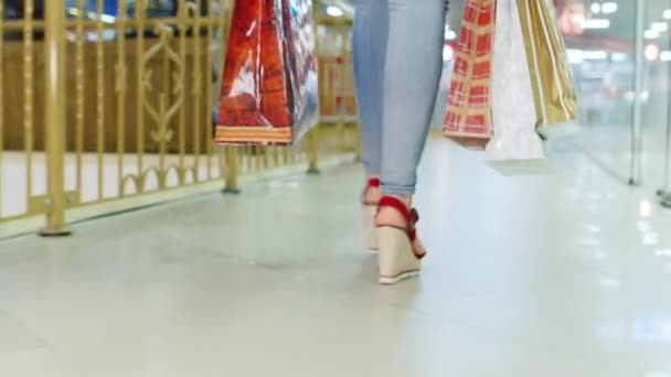 e56ad23f5e Mujer joven en pantalones vaqueros y zapatos rojos caminando en el centro  comercial. Vista trasera