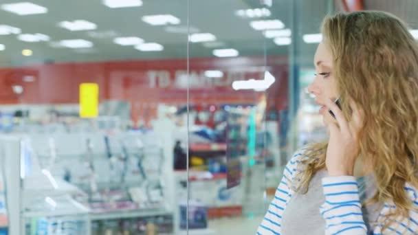 Atraktivní ženské shopper s dyal nákupní tašky stojící na výloze, mluví do mobilu