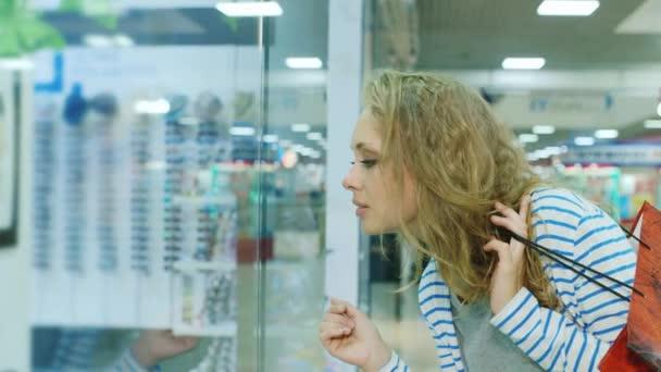 Fiatal nő keresi a kirakatba bevásárló táskák