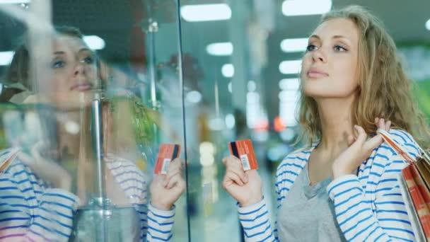 Atraktivní mladá žena při pohledu na skleněné vitríně v úložišti. Ruce držící kartu pro nakupování a nákupní tašky