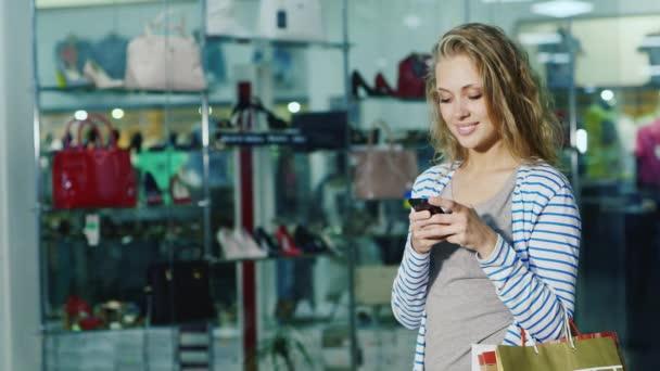 A bevásárló szatyrok vonzó női shopper használ egy smartphone. Szemben az üveg vitrinek cipőbolt