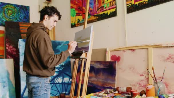 Young handsome painter working in the studio. He draws a picture paints