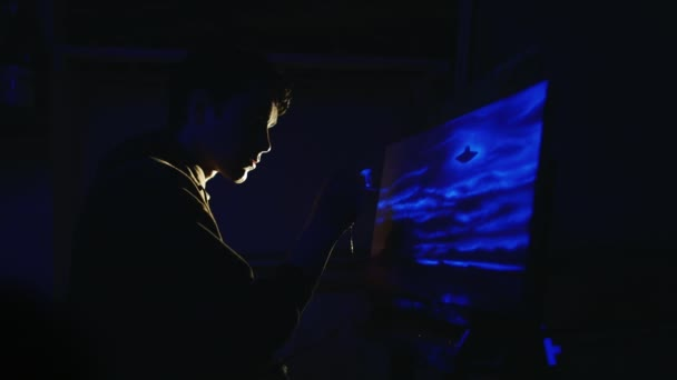 The artist draws a picture in ultraviolet light. In the picture, glowing clouds and unrecognized flying object