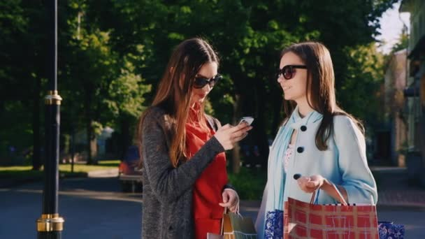Two girl friends with shopping bags used smartphone outdoor